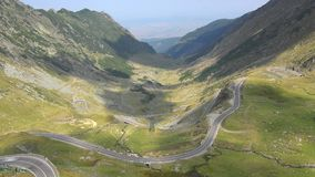 Timelapse of cars on winding road and clouds shadows on mountains. UHD 4K stock footage