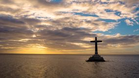 Timelapse: Sunken Cemetery cross in Camiguin island, Philippines. Timelapse: Catholic cross in sunken cemetery in the sea at sunset, aerial view. Colorful stock video footage