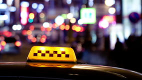 Timelapse of city traffic at night behind taxi sign stock video