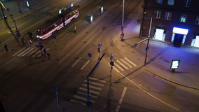 Timelapse of city traffic in Tallin in the evening. Timelapse of night Tallin with its city traffic. High angle view of crossroad with zebra crossings and tram stock video footage