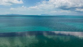 Timelapse of clear pool with great picturesque sea view. Villa on the Ocean Bay with Clouds Reflection in Panoramic Pool. 4k UHD stock video footage