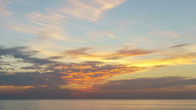 Timelapse of clouds crossing the amazing sky over the sea or ocean at sunset. 4K/UHD Day to Night Time-lapse : Timelapse of clouds crossing the amazing sky over stock footage