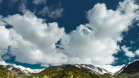 Timelapse clouds drifting along top of rocky mountain peaks stock footage