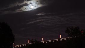 Timelapse Clouds moving past a full moon in the night sky and Xi`an city wall, xi`an, shaanxi, China stock footage