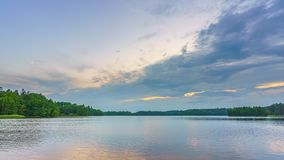 Timelapse of clouds over forest lake stock video footage