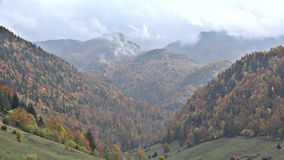 Timelapse of clouds rising up the mountains, colorful autumn landscape. UHD 4K stock footage