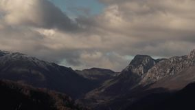 Timelapse - Clouds Swim Over Beautiful Mountains. Timelapse - White Cumulus Clouds Swim Over Picturesque Beautiful Mountains Covered With Snow In The Autumn Time stock video footage