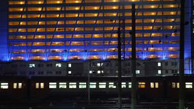 Timelapse of commuter train in the city at night. Timelapse of electric train passing by the lighted building in the city at night stock video