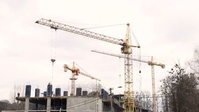 Timelapse construction industry. Three cranes and a group of workers are building a house.