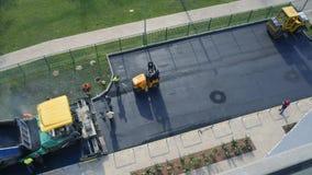 Timelapse. Constructions workers working on road. Asphalt paver applying hot asphalt on the highway. Steamroller flatten stock footage