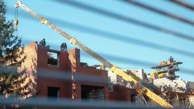 Timelapse, construtores está trabalhando no canteiro de obras o guindaste levanta a carga a uma altura construção dos trabalhador video estoque