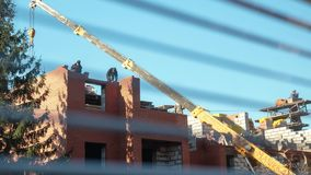 Timelapse, construtores está trabalhando no canteiro de obras o guindaste levanta a carga a uma altura construção dos trabalhador filme