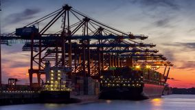 Timelapse of Container Terminal. Timelapse of contianer cranes loading and unloading a huge container ship in the port of hamburg during sunset stock footage