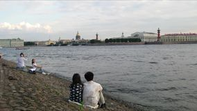 Timelapse of a couple sitting on the bank of the Neva River stock video footage