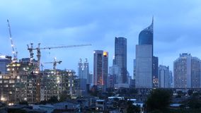 Timelapse of crane and buildings under construction. JAKARTA, Indonesia. October 12, 2017: Timelapse footage of crane and high rise buildings under construction stock footage