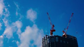 A timelapse of cranes at the under construction behind the blue sky in Tokyo. A time lapse of moving cranes at the under construction behind the blue sky stock video footage