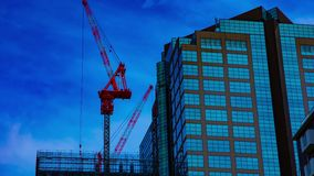 A timelapse of cranes at the under construction on the building in Tokyo stock video footage
