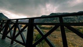 Timelapse da cerca de madeira no terraço alto na paisagem da montanha com nuvens Movimento horizontal do slider filme