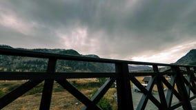 Timelapse da cerca de madeira no terraço alto na paisagem da montanha com nuvens Movimento horizontal do slider video estoque