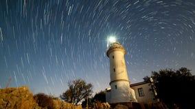 Timelapse da paisagem bonita da noite com o farol com giro do céu estrelado em um fundo vídeos de arquivo