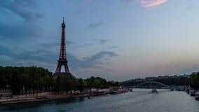 Timelapse da torre Eiffel que ilumina-se acima após o por do sol, com os barcos da excursão que passam perto no Seine River, vist vídeos de arquivo