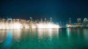 Timelapse dansende die fontein dichtbij Burj Khalifa door de stad bij nacht wordt verlicht stock footage