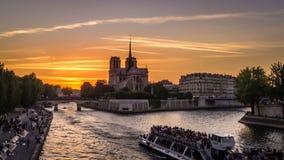 Timelapse de barcos en París en la puesta del sol, con la iglesia del Notre-Dame de Paris en el fondo y la gente que descansan so almacen de metraje de vídeo