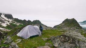 Timelapse de caminhar o homem do turista perto do smartphone do uso da barraca em montanhas nevado altas vídeos de arquivo