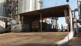 Timelapse de descargar los camiones del grano en el elevador en la elevación del descargador hidráulico de la plataforma Transbor almacen de video