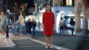Timelapse de femme se tenant toujours sur la rue égalisante serrée tandis qu'une tache floue des personnes rapides se déplacent a clips vidéos