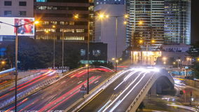 Timelapse de Hong Kong Business District en la noche Edificio corporativo en el tráfico trasero y ocupado a través de la carreter almacen de metraje de vídeo