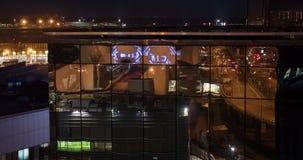 Timelapse de la ciudad que refleja en el edificio vidrioso, opinión de la noche almacen de metraje de vídeo