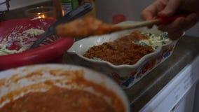 Timelapse de la mujer que monta un plato de las lasañas en cocina almacen de metraje de vídeo
