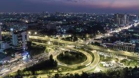 Timelapse de la opinión aérea del paisaje urbano en la noche Bangkok, tráfico ocupado a través de la carretera principal en la ho