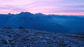 Timelapse de la puesta del sol sobre picos de montaña Sun pasa abajo picos agudos de las montañas Cielo púrpura rosado Flama colo almacen de metraje de vídeo