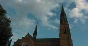 Timelapse de uma igreja velha, de umas nuvens moventes e de um céu azul em Upsália filme