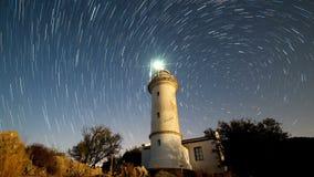 Timelapse del paisaje hermoso de la noche con el faro con la rotación del cielo estrellado en un fondo almacen de metraje de vídeo