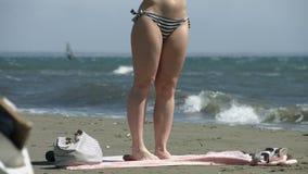 Timelapse del soggiorno della donna sulla spiaggia durante la vacanza, tempo tempestoso, onde spumose video d archivio