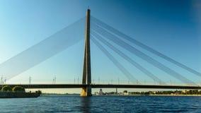 Timelapse del tráfico en el puente de cable en Riga con la gente canoeing cerca almacen de video