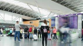 Timelapse della gente è stante e guardante il programma di volo all'aeroporto I turisti stanno aspettando il loro aereo stock footage