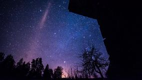 Timelapse des étoiles au-dessus de la maison de bois de construction la nuit hiver banque de vidéos