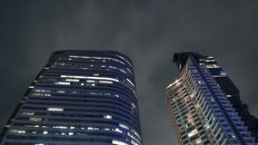 Timelapse des gratte-ciel avec les nuages de nuit mobiles Illumination de la ville de nuit banque de vidéos