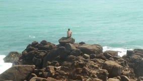 Timelapse des Mannes sitzend auf einem enormen Flussstein auf einem Strand und das Meer betrachtend stock footage