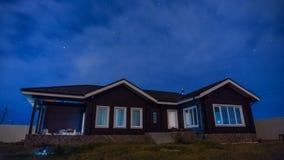 timelapse di notte 4K con una bella casa, il movimento delle stelle e nuvole nel cielo notturno archivi video