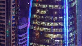 Timelapse di Windows della costruzione multipiana dell'illuminazione di vetro e d'acciaio e dei lavoratori dell'ufficio dentro stock footage
