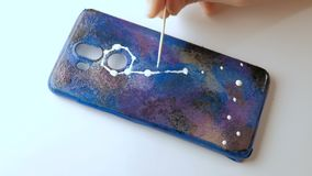 DIY. Timelapse. Hand of a teenager draws a zodiac sign on a background of the starry sky. Hand-made mobile phone case. Timelapse. DIY. Hand of a teenager draws stock footage