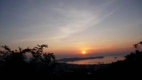 Timelapse do nascer do sol sobre a ilha Vista de ramos de ?rvore, de ba?a com navios, das nuvens de prata e de nuvens escuras vídeos de arquivo