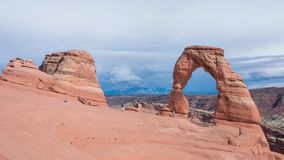 Timelapse dos turistas que são fotografados contra o arco delicado no parque nacional dos arcos, fluxo das nuvens, Utá, EUA, 4k filme