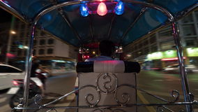 Timelapse of driving tuktuk in night Bangkok, Thailand. Timelapse shot of a man driving tuktuk taxi on the roads of night Bangkok, Thailand. View from passenger stock footage