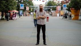 Timelapse du jeune homme barbu se tenant tranquille au trottoir dans le courant du trafic de foule avec des personnes se déplaçan clips vidéos